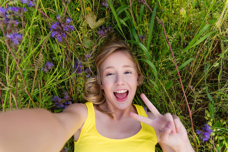 Girl in purple flowers outdoors in summer stock image