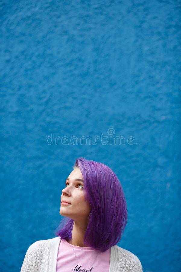 Girl with purple hair on blue background royalty free stock images