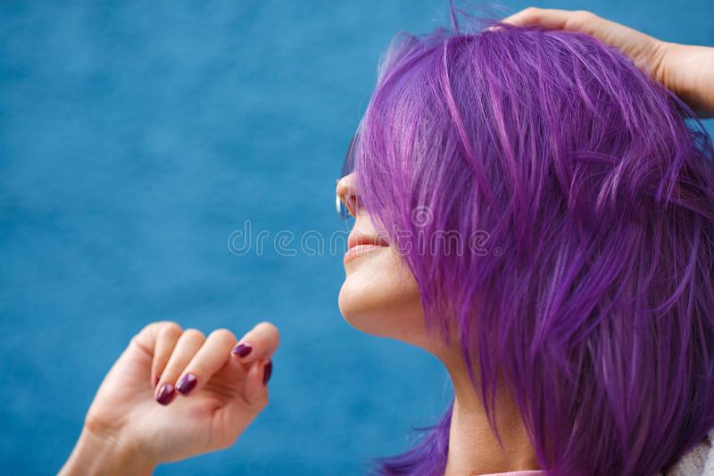 Girl with purple hair on blue background stock photography