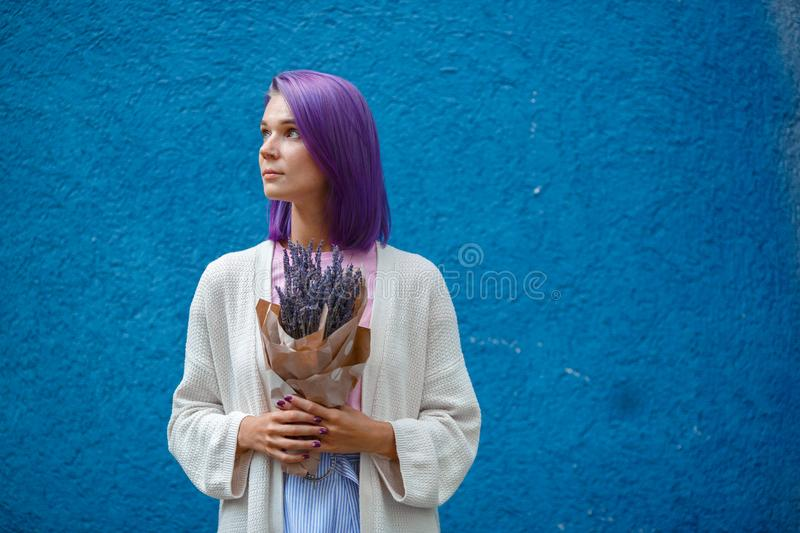 Girl with purple hair holds a bouquet of lavender stock image