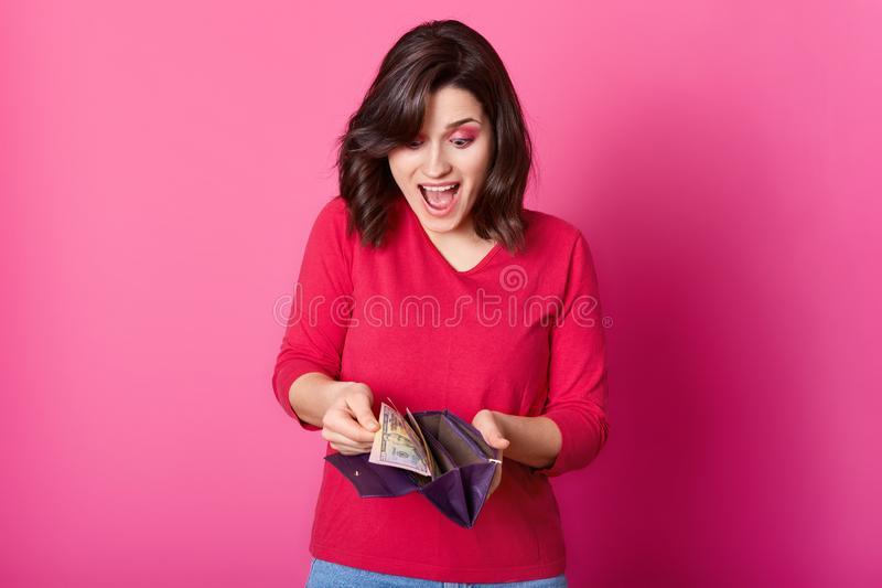 Girl with purple wallet full of money in hands looks astonished. Surprised woman wears shirt, holds opened purse, being glad to stock images