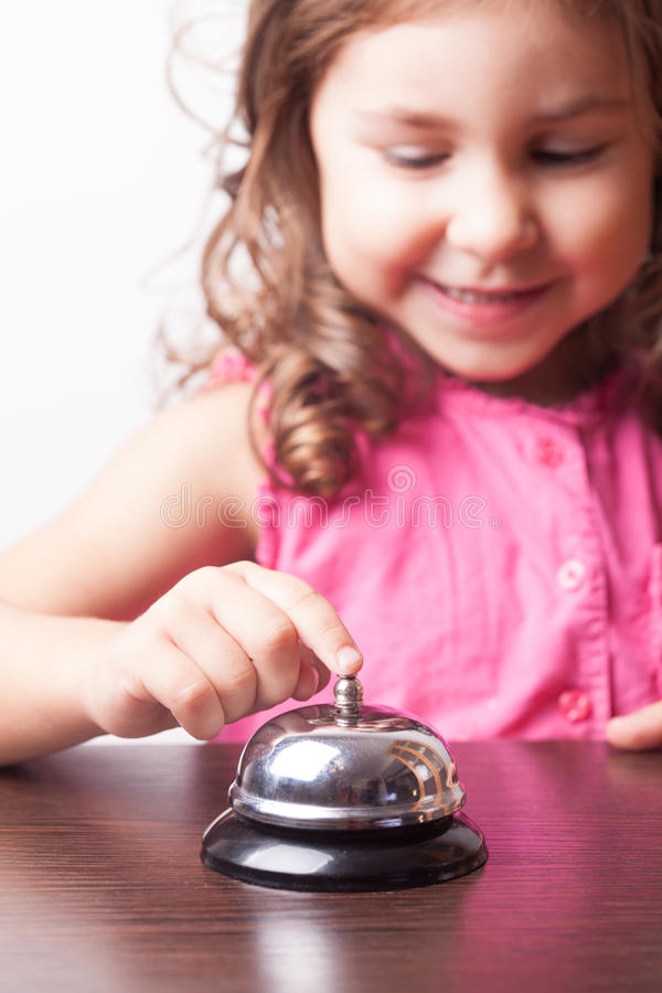 Girl push on the bell. Little pretty girl push on the bell, board game on time royalty free stock images