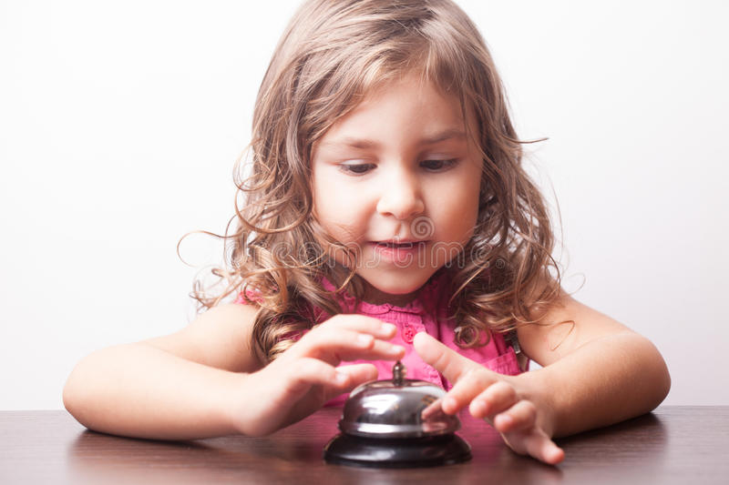 Girl push on the bell. Little pretty girl push on the bell, board game on time royalty free stock photography