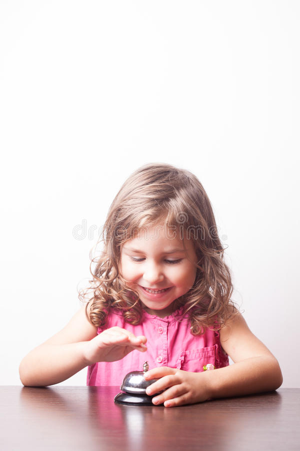 Girl push on the bell. Little pretty girl push on the bell, board game on time royalty free stock image