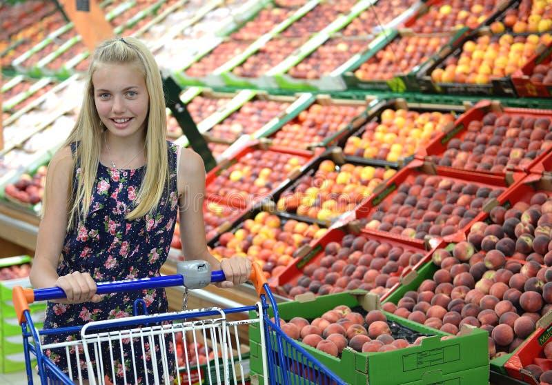Girl Pushing Shopping Cart in Fruit Market. Young girl in grocery store pushing a metal shopping cart in the fruit section stock photo