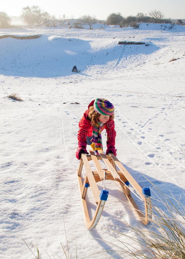 Girl pushing a sledge royalty free stock photography