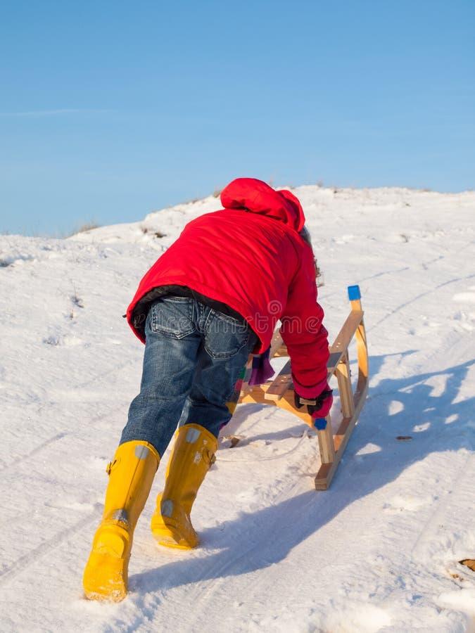 Girl pushing a sledge royalty free stock photo