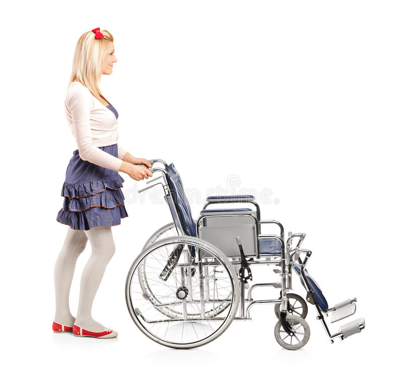 Girl pushing a wheelchair royalty free stock photography