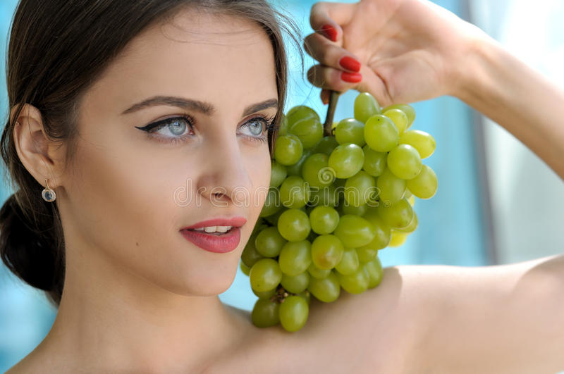 Girl put a bunch of green grapes on her left shoulder. Girl put a large bunch of ripe green grapes on her left shoulder and she looks away. Beauty portrait with stock photography