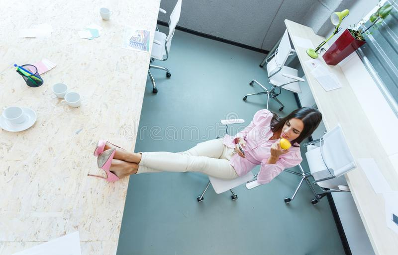 The girl put her feet on the desk in the office. stock images