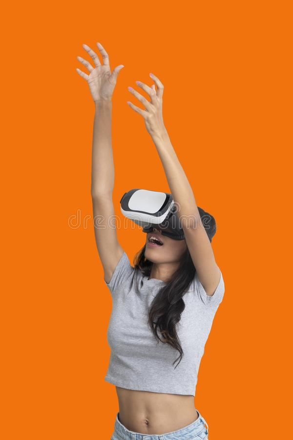 Girl put her hands up while playing multimedia game with virtual reality glasses stock image