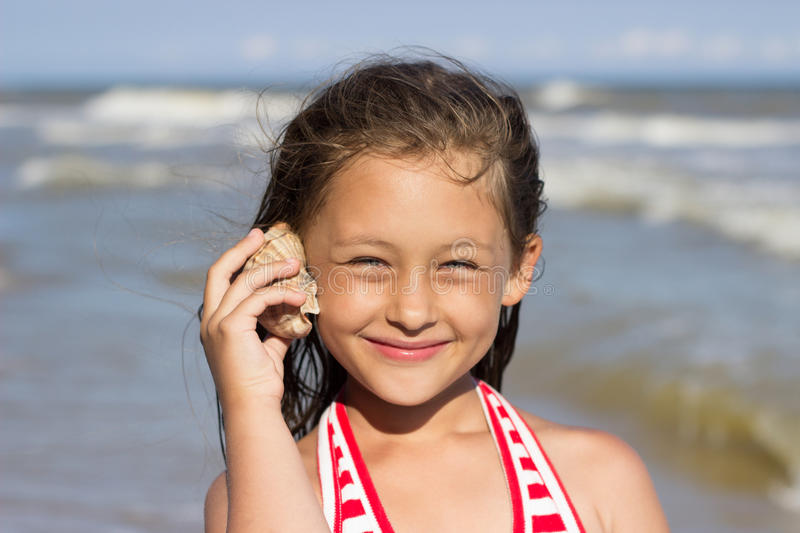 Girl put to the ear sea shell royalty free stock image