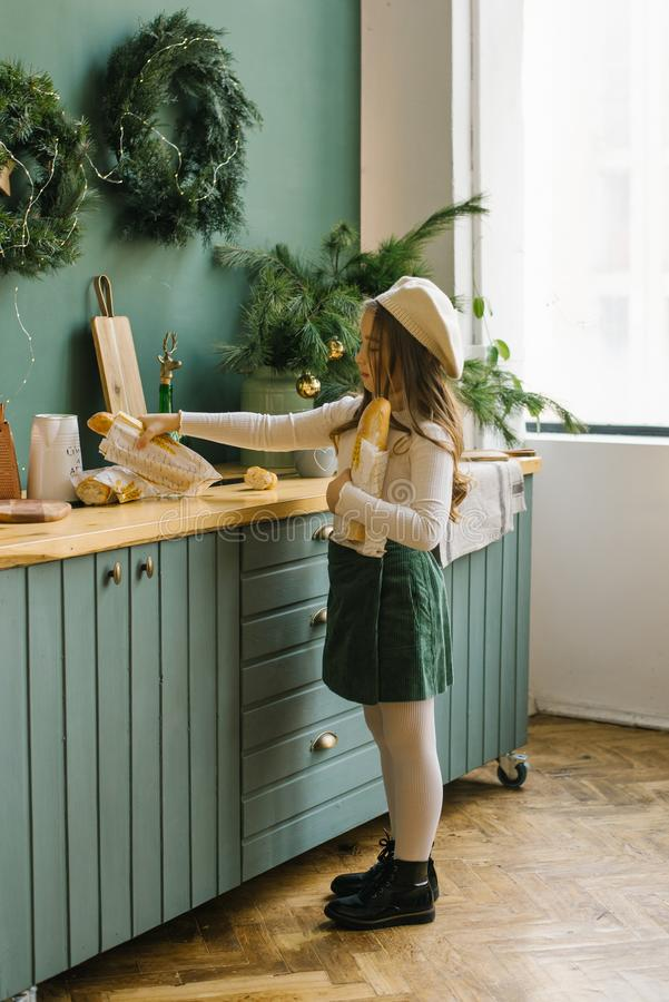 Girl puts on Christmas kitchen baguette on the table. Stylish girl puts on Christmas kitchen baguette on the table royalty free stock images