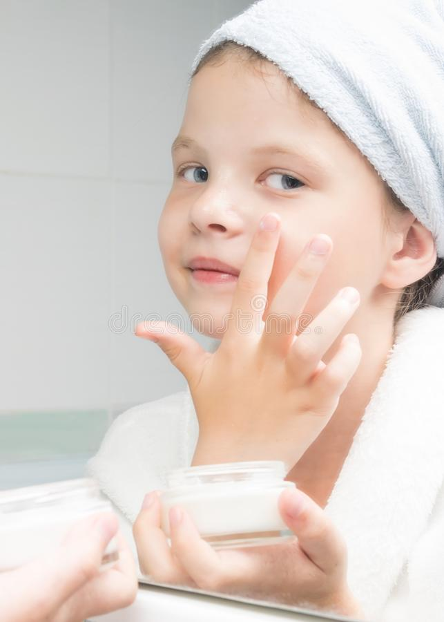 Girl puts cream on her face standing in front of a mirror after a shower. Girl puts cream on her face standing in  front of a mirror after a shower stock photo