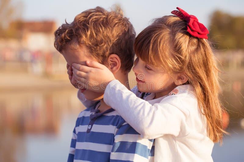 Girl puts hands on boys eyes stock photos