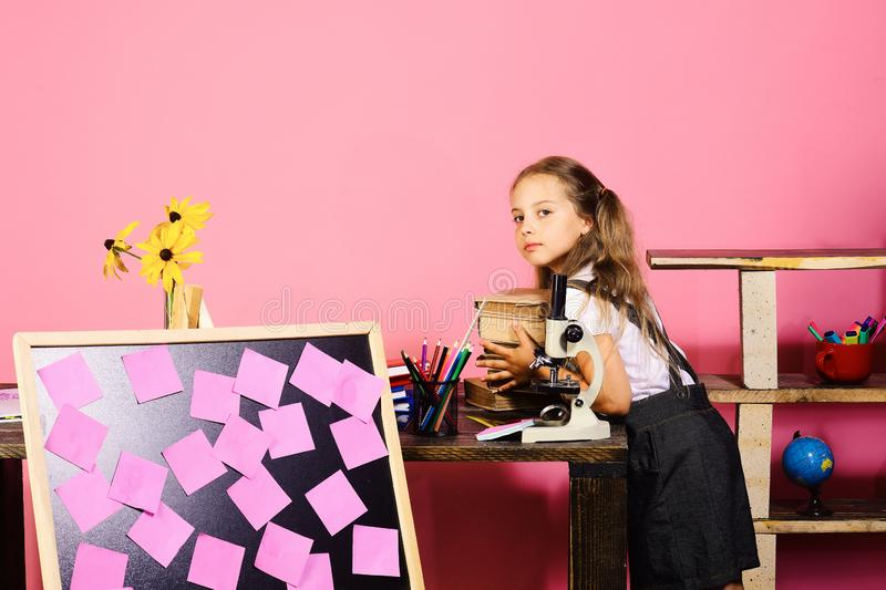 Girl puts books on desk with microscope and blackboard royalty free stock photos