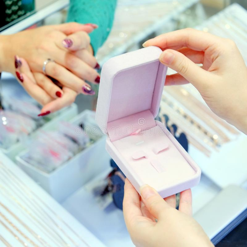 The girl puts the ring on the finger. Empty jewelry box in the female hands of the seller. Shop gold products. Square frame stock photography