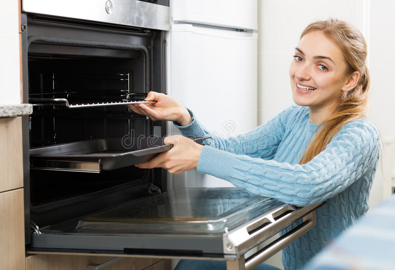 Girl putting baking tray in kitchen oven. Portrait of young girl putting baking tray in kitchen oven royalty free stock image