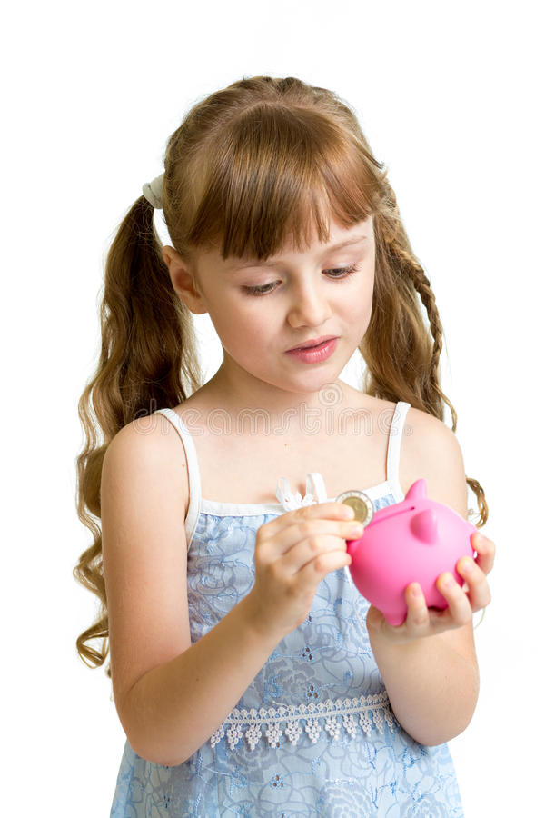 Girl putting coin into piggy bank stock photography