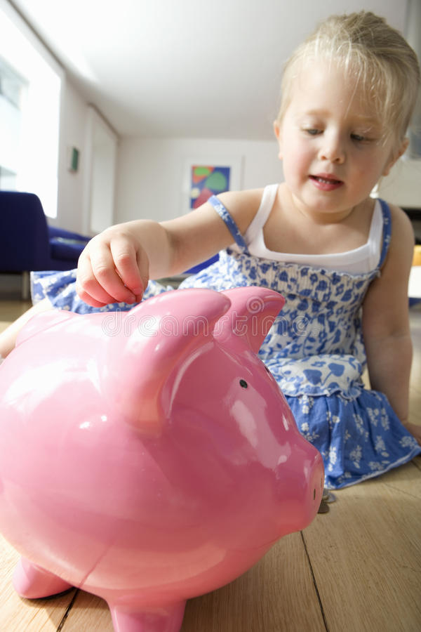 Girl (2-4) putting coin in piggy bank, low angle view stock image