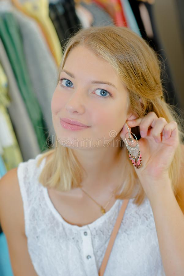 Girl putting on earrings. A girl putting on earrings royalty free stock photography