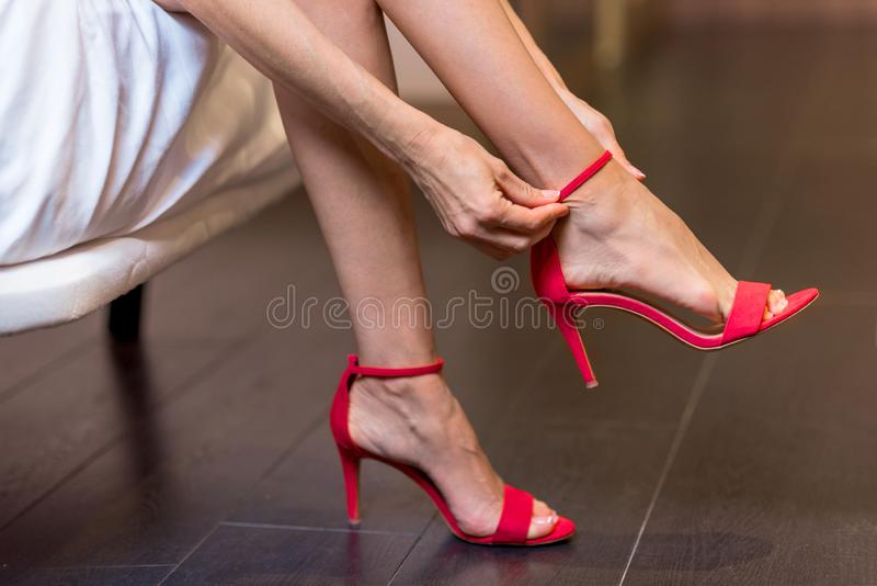 Girl putting her red high heels shoes on.  royalty free stock images