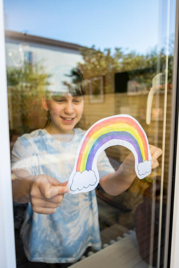 Girl Putting Picture Of Rainbow In Window At Home During Coronavirus Pandemic To Entertain Children. Girl Puts Picture Of Rainbow In Window At Home During royalty free stock photo