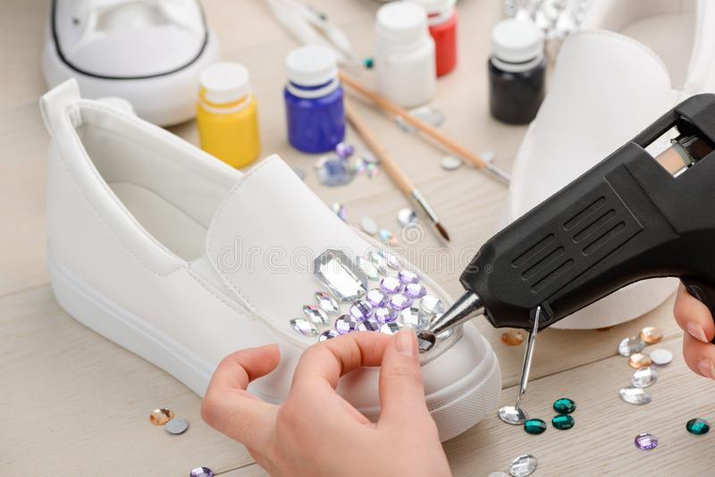 Girl putting a rhinestone. Onto slip-on shoe using a hot glue gun. Awesome DIY footwear design royalty free stock image