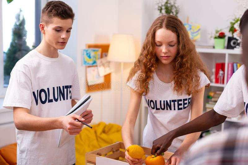 Girl putting vegetables and fruits into box gathering food for donation royalty free stock photo
