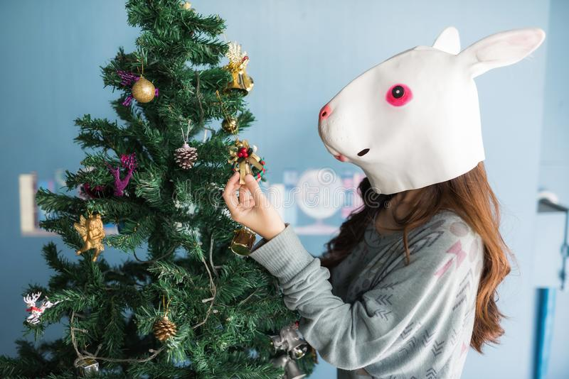 Girl with rabbit mask decorated Xmas tree royalty free stock images
