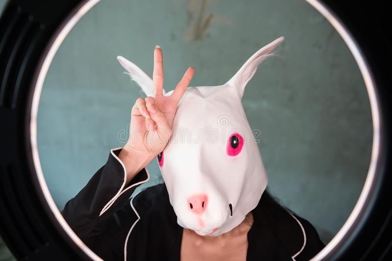 Girl with rabbit mask with v sign stock image