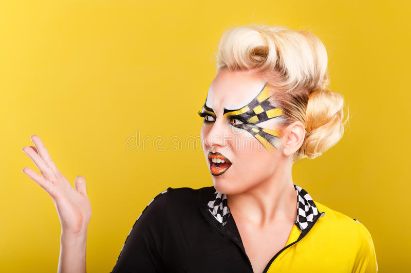 Girl racer is outraged. On yellow background. Girl racer is outraged. Attractive girl with face art. Sport suit. Race. Emotions. On a yellow background royalty free stock photography