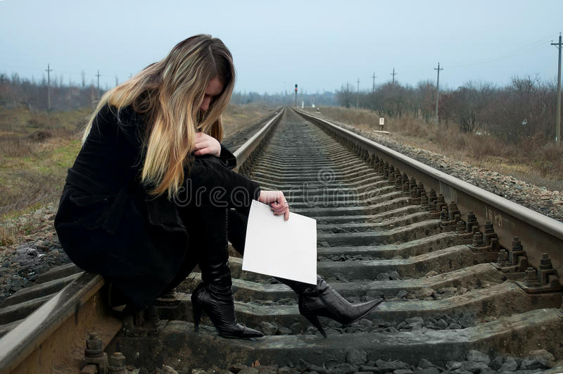The girl on rails. The lonely girl sits on rails with a sheet of paper in hands royalty free stock photos