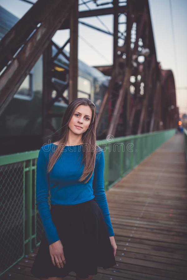 Girl on a railway station with a leaving train. Urban sunset portrait stock images