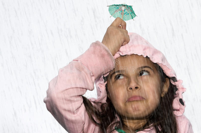 Girl in rain. A little girl holding a cocktail umbrella in the rain royalty free stock image
