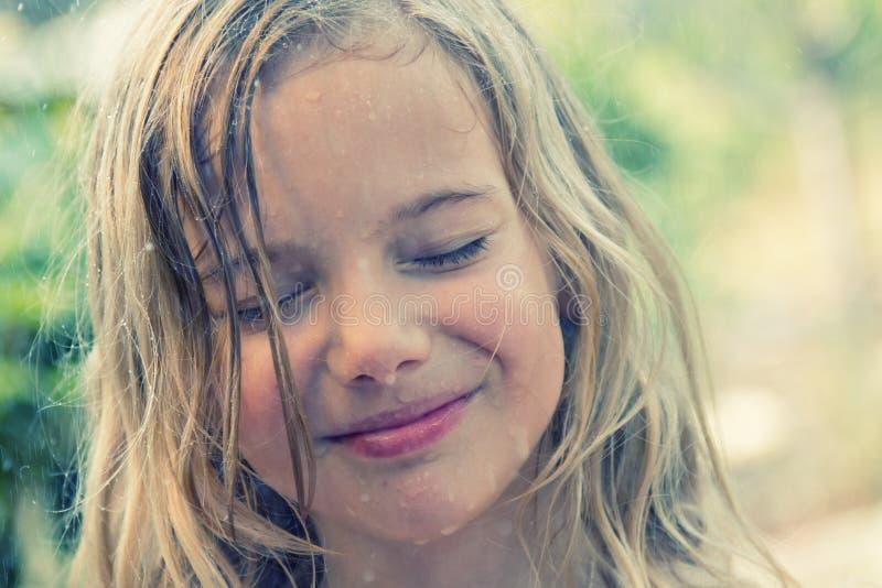 Girl in rain. A smiling girl enjoying the fresh rain in spring royalty free stock photo