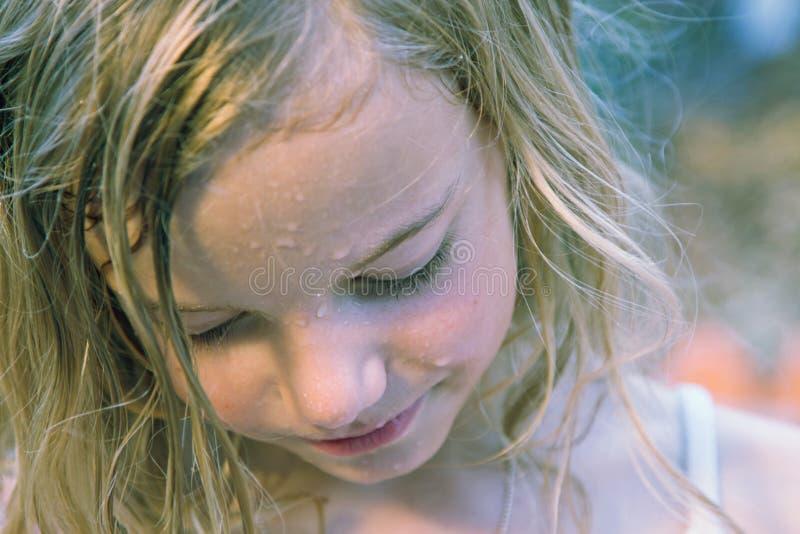 Girl in rain. A little girl enjoying the fresh rain in spring royalty free stock photography