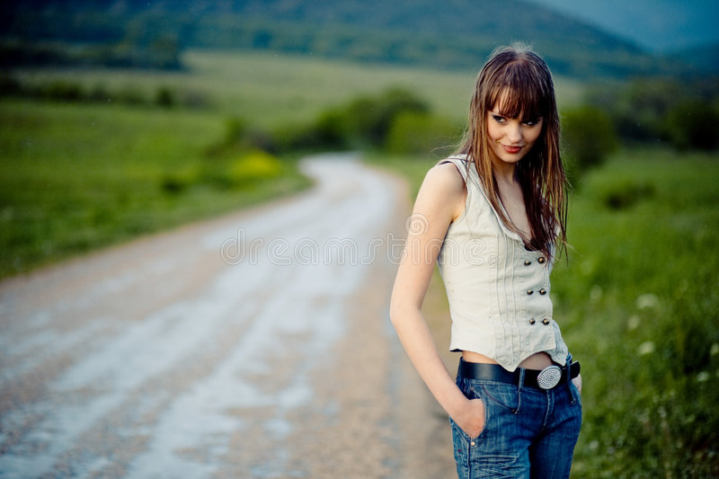 Girl after rain. Young lonely teenager girl with wet hair staying on road after rain royalty free stock images