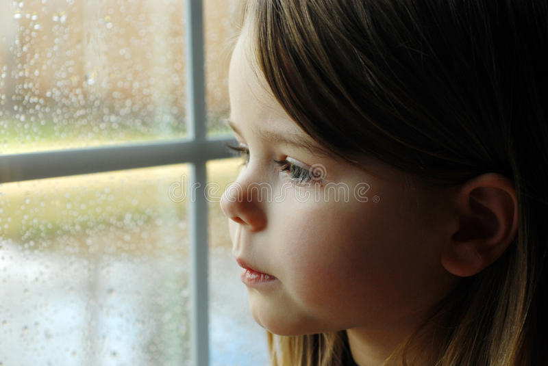 Girl and rain. Wet glass autumn bad weather royalty free stock photography