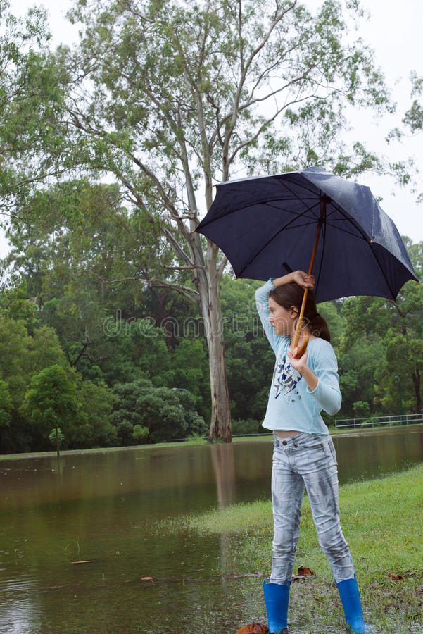 Girl in the rain. Young girl in the rain carrying and umbrella, close to a flooded area in a park royalty free stock photo