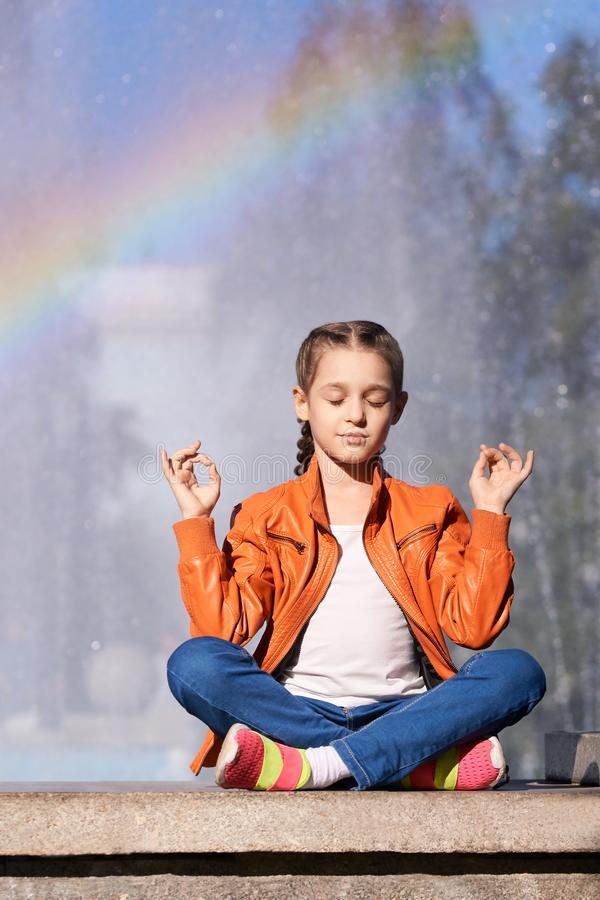Girl with rainbow sitting outdoors. one person class retreat. training soul. serene outside stock images