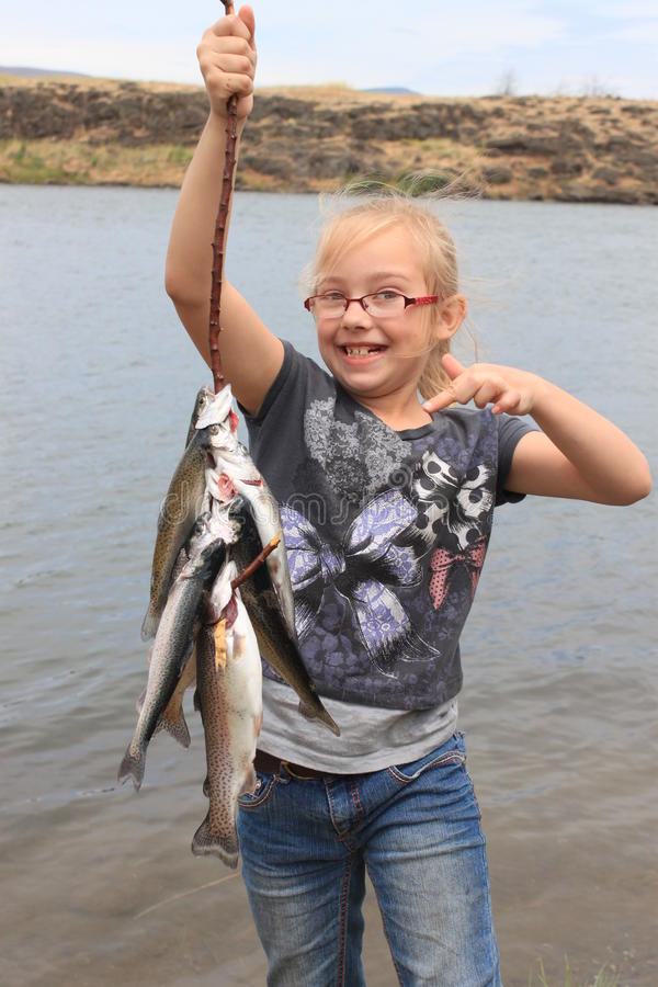 Girl with Rainbow Trout royalty free stock image