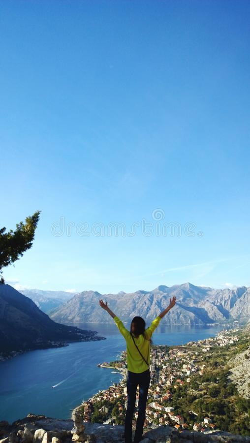 Girl with raised arms happy journey. Admiring the Boka Bay in Montenegro. Vertical view.  stock photography