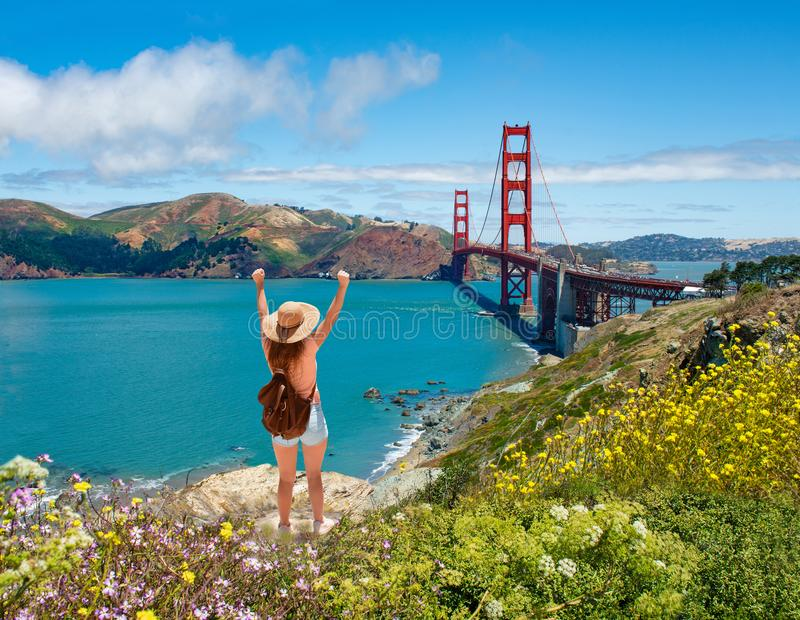 Girl with raised hands relaxing on top of the mountain, enjoying beautiful view. Hiking trip. Golden Gate Bridge, over Pacific Ocean and San Francisco Bay, San royalty free stock photo