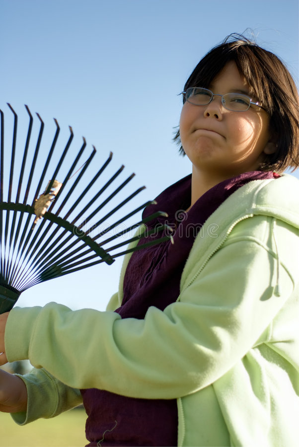 Girl Raking Leaves. A nine year old girl holding a rake is going to rake leaves royalty free stock photos