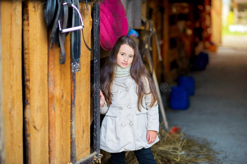 Girl at a ranch, stands by the stables waiting for her horse. A girl at a ranch, stands by the stables waiting for her horse stock image