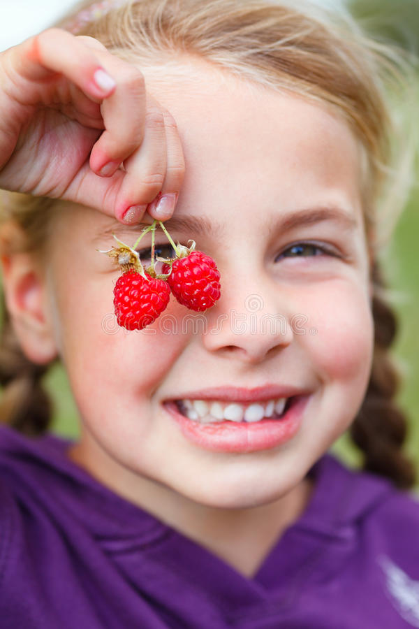 Girl with raspberries royalty free stock photos
