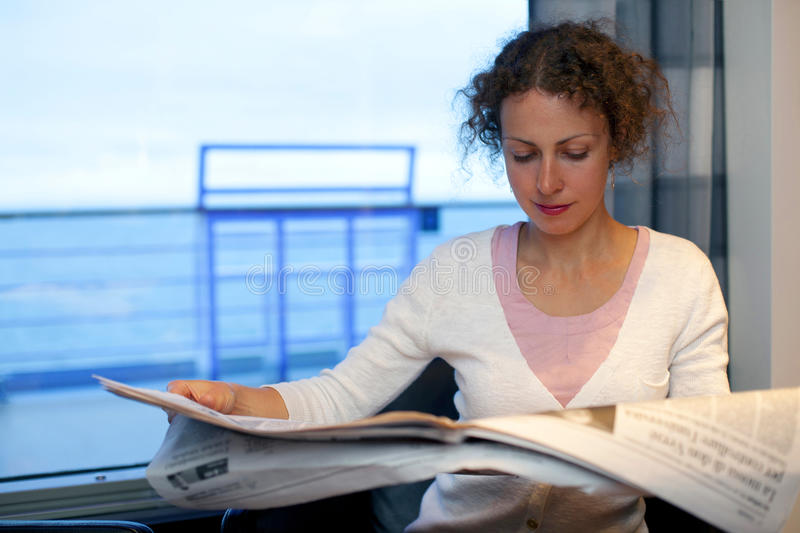 Girl read newspaper in cabin of big ship royalty free stock photography