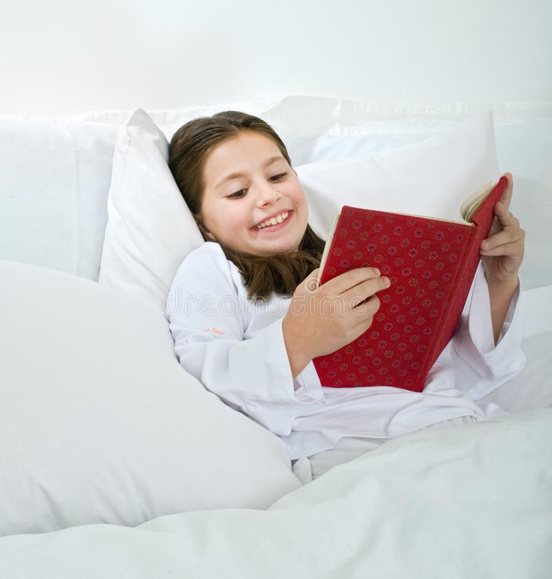 Girl reading in bed stock photography