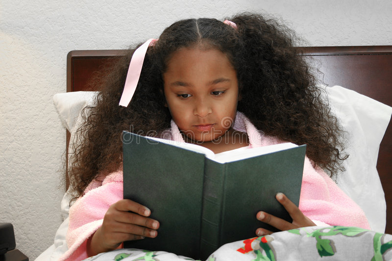 Girl reading in bed. A little African American girl reading a book in bed royalty free stock photography